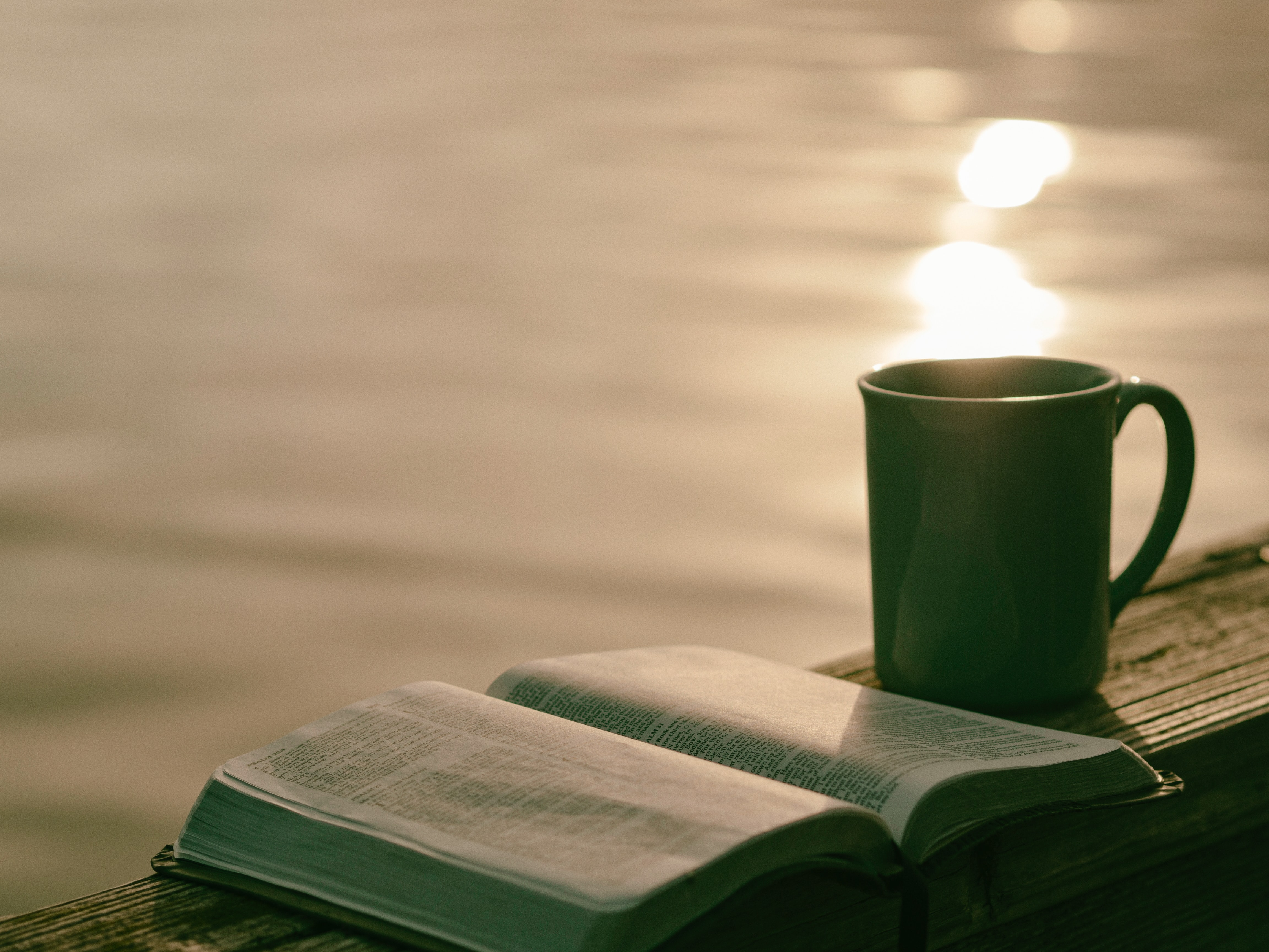coffee and a bible by the water