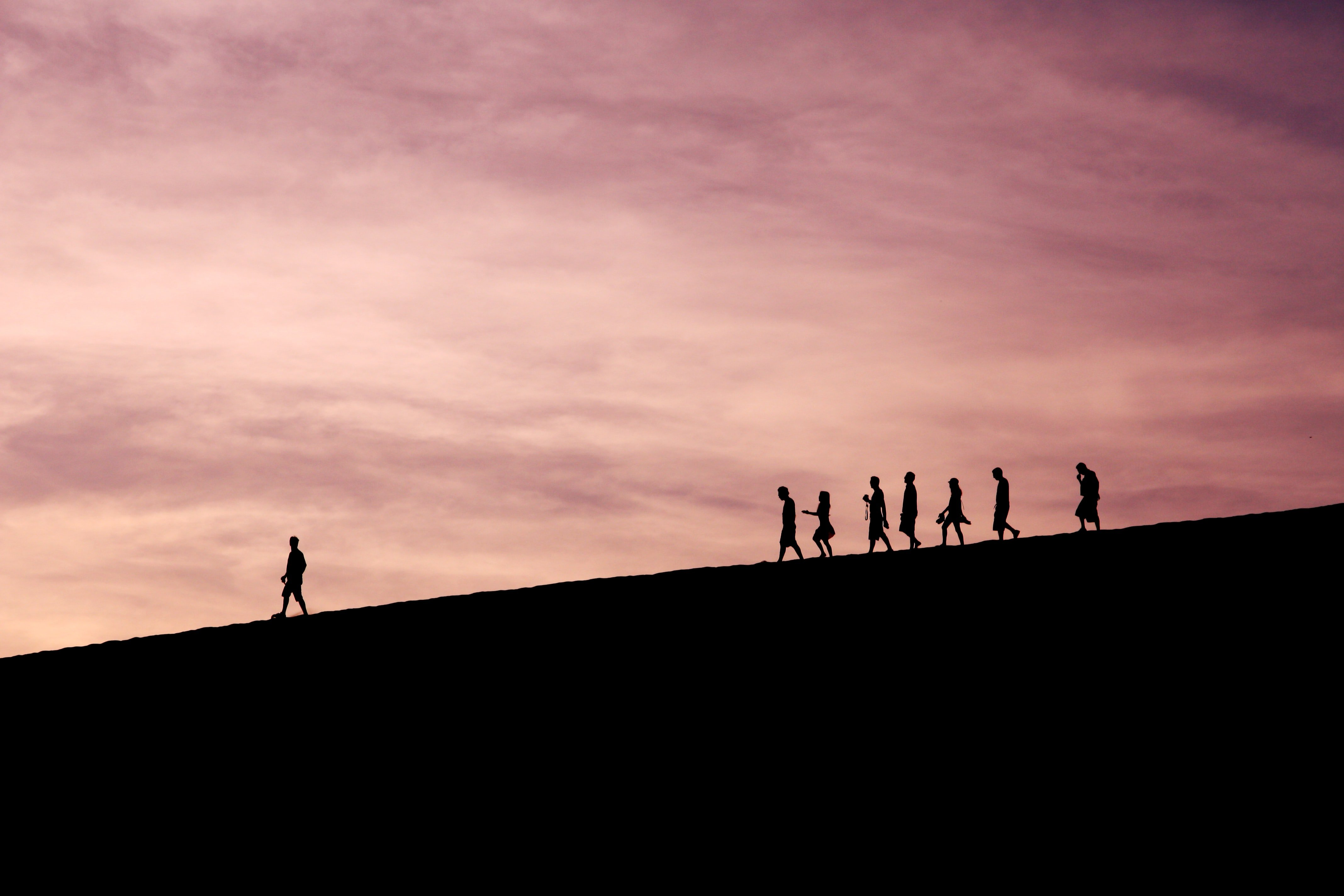 group of silhouettes running down hill, one ahead of others
