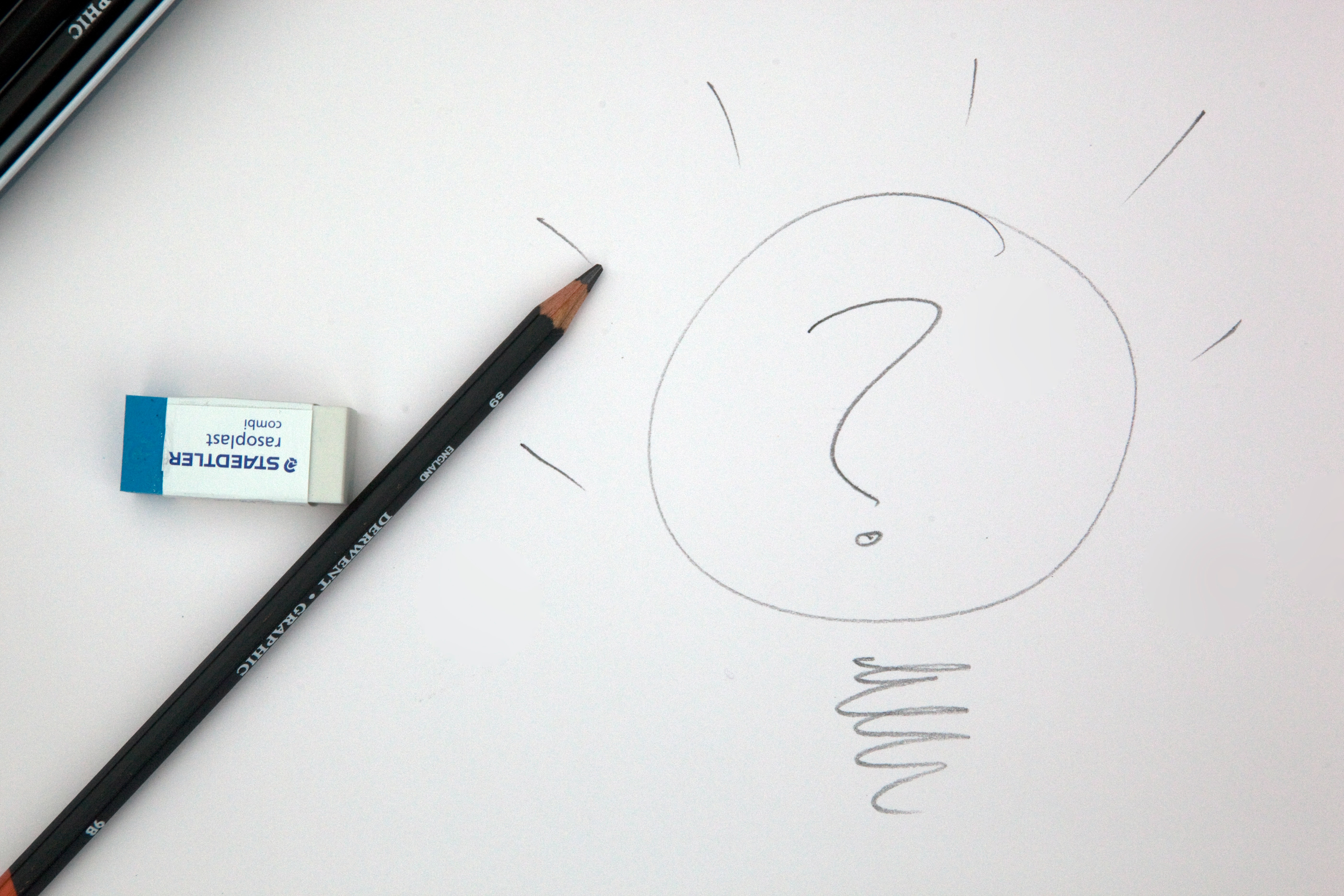 pencil and eraser on a piece of paper with a lightbulb and question mark written