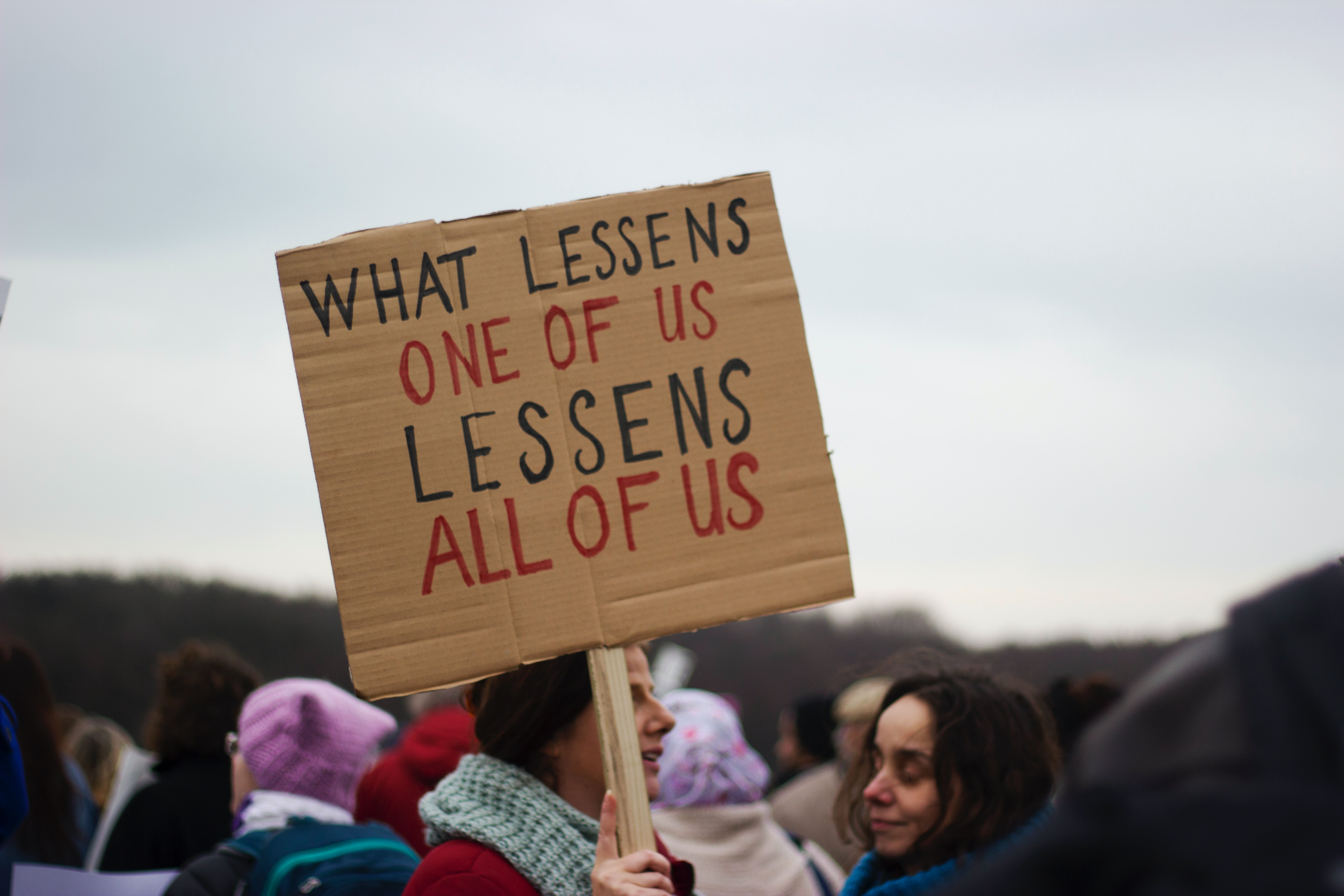protest sign - what lessens one of us lessens all of us